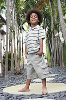 Boy (5-6 years) standing on stepping stone on path portrait low angle view