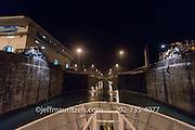 The Gatun locks in the Panama canal are opened to a ship at nighttime.