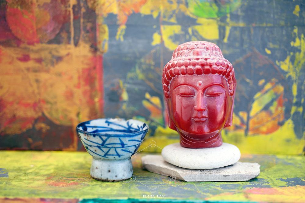Antique buddha head and wabi-sabi saki cup.