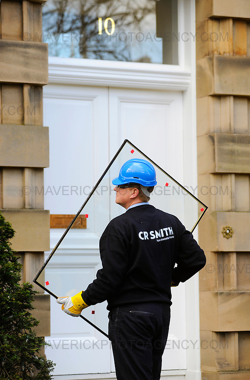 """The Edinburgh home of former Royal Bank of Scotland boss Sir Fred Goodwin has been attacked by vandals.  Windows were smashed and a Mercedes S600 car parked in the driveway was vandalised.  Police said they were investigating these claims as part of their inquiry, adding that they took planned attacks """"very seriously"""". Pictured CR Smith glaziers repair the windows."""