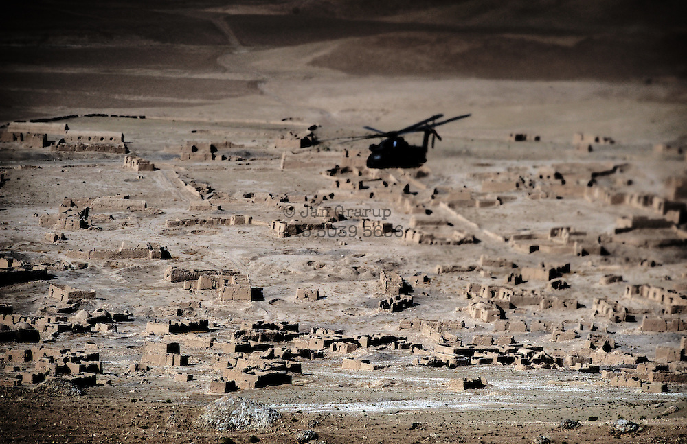 A armoured german ISAF helicopter passing a mountain village  during a patrol .<br /> due to the treat from taliban and insurgents the helicopters fly tactical flying which means that they fly low and fast during the patrols.Taliban frequently attack with handweapon and rockets from abandoned villages whenever they meet ISAF troops. <br /> For more caption info, please contact photographer.