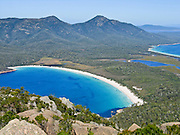 See Wineglass Bay and protected wilderness from atop Mount Amos Track, on the Hazards, in Freycinet National Park, Tasmania, Australia. Devonian Granite is the dominant rock type at Freycinet. Orthoclase, a pink feldspar gives the mountains and coastline their characteristic pink tint. Black micas and white quartz are also found. The Tasman Sea is part of the South Pacific Ocean.