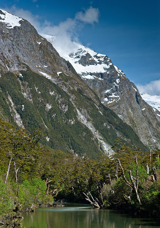 Beech tree-lined river beneath the snow-capped peaks of the Clinton Canyon, Milford Track, Fiordland, New Zealand