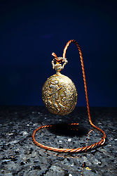 A gold colored pocket watch is displayed on a stand made of three strands of twisted copper wire which sits on a piece of polished marble all against a blue backdrop.  The timepiece is lighted from above by a single strobe with a snoot attached.