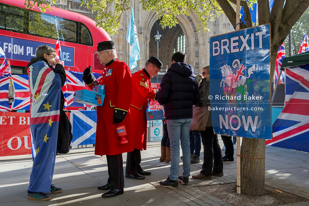 On the day that the EU in Brussels agreed in principle to extend Brexit until 31st January 2020 (aka 'Flextension') and not 31st October 2019, two Chelsea Pensioners sell Remembrance poppies, next to Brexit Party flags and banners during a Brexit protest outside parliament, on 28th October 2019, in Westminster, London, England.