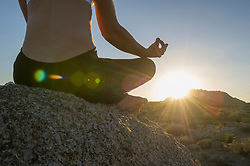 Woman sitting in lotus position on boulder at sunrise (Credit Image: © Image Source/Les & Dave Jacobs/Image Source/ZUMAPRESS.com)