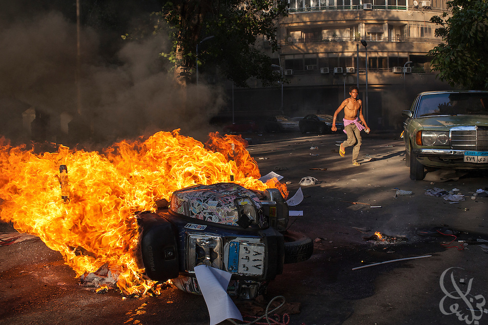 An opponent of deposed Egyptian President Mohamed Morsi runs behind a torched scooter of Pro-Mosi supporters  following violent clashes between the two factions July 22, 2013 in the Garden City district of Cairo, Egypt. Fighting between the two sides broke out near Tahrir Square in the late afternoon, and the subsequent running battles with rocks and guns through narrow city streets saw at least one killed.