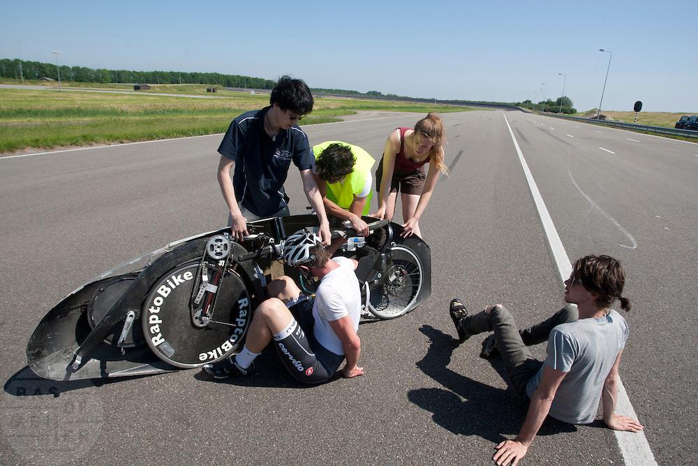 Jan Bos stapt uit de oude Velox na zijn val, rechts is het valspoor te zien. Het Human Powered Team van de TU Delft en de VU Amsterdam testen op de RDW baan in Lelystad voor het eerst met de fiets, de Velox 2, waarmee ze het record willen verbreken.<br /> <br /> Jan Bos is getting out of the old Velox after his crash. The Human Powered Team is testing at the RDW test track in Lelystad for the first time with the new bike, the Velox 2,  which they want to set the world record with.