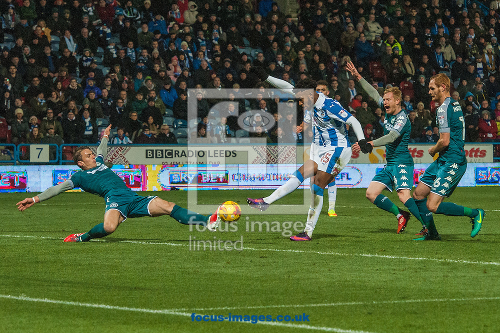 Kasey Palmer of Huddersfield Town sees his shot on goal blocked by Stephen Warnock of Wigan Athletic during the Sky Bet Championship match at the John Smiths Stadium, Huddersfield<br /> Picture by Matt Wilkinson/Focus Images Ltd 07814 960751<br /> 28/11/2016