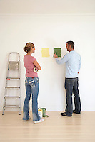 Woman watching man testing paint colours on wall