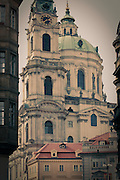 The Baroque architecture of St. Nicholas Cathedral in Prague rendered in antique look.