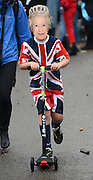 © Licensed to London News Pictures. 03/06/2012. London, UK. A young boy pushes a scooter dressed in a union flag outfit and Queen mask. Boats gather at Hammersmith and Putney at their muster points before taking part in the Jubilee Padgeant. The Royal Jubilee celebrations. Great Britain is celebrating the 60th  anniversary of the countries Monarch HRH Queen Elizabeth II accession to the throne this weekend Photo credit : Stephen Simpson/LNP