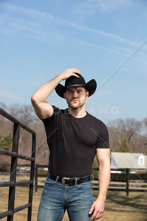 cowboy holding on to his cowboy hat on a ranch