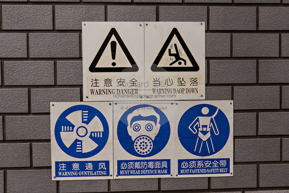 Civil defense emergency warning signs misspelt on a wall in Beijing, China