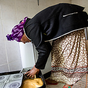 Hailù's mother tries to pack the pieces of the traditional coffee box in her suitcase, together with several sacks of flour for the enjira
