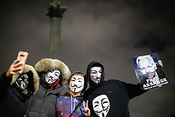"""© Licensed to London News Pictures . 05/11/2019. London, UK. A man holds """" Free Assange """" poster as other take a selfie in front of Nelson's Column in Trafalgar Square . Supporters of Anonymous , many wearing Guy Fawkes masks , attend the Million Mask March bonfire night demonstration , in Trafalgar Square in central London . Photo credit: Joel Goodman/LNP"""