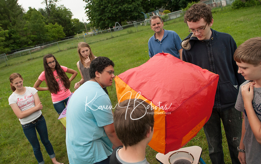 Belmont Middle School's 8th grade teacher Mr. White watches as his students Alex Gilbert, Dakota Wright, Bryan Underhill and Drew Taylor send off their hot air balloon created during Science class.   (Karen Bobotas/for the Laconia Daily Sun)