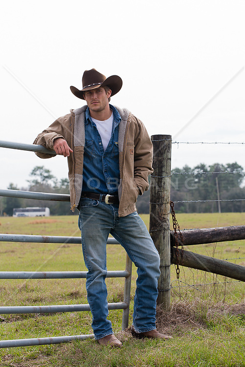 cowboy leaning on a gate at a ranch