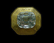 Topaz.  A large colourless faceted stone in an engraved gold setting.