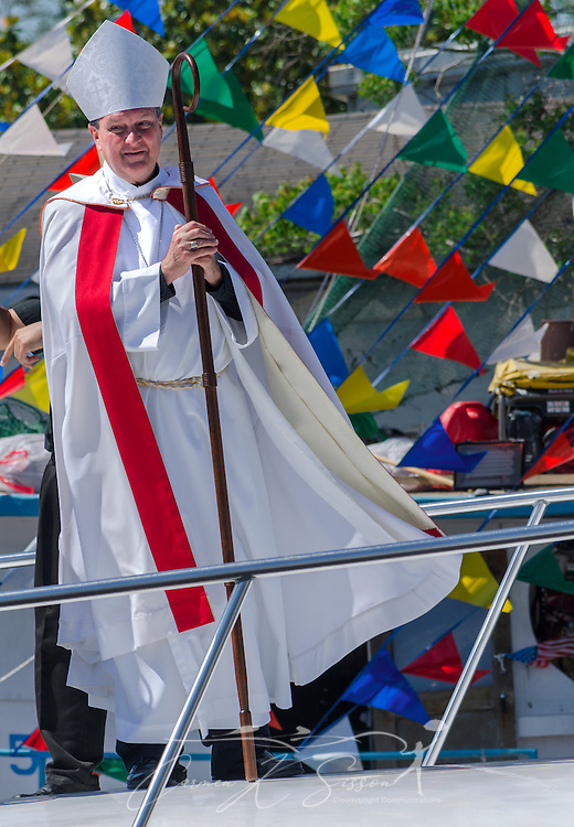 Catholic Archbishop Thomas J. Rodi stands on the deck of a boat during the 65th annual Blessing of the Fleet in Bayou La Batre, Alabama, May 4, 2014. The first fleet blessing was held by St. Margaret's Catholic Church in 1949, carrying on a long European tradition of asking God's favor for a bountiful seafood harvest and protection from the perils of the sea. The highlight of the event is a blessing of the boats by the local Catholic archbishop and the tossing of a ceremonial wreath in memory of those who have lost their lives at sea. The event also includes a land parade and a parade of decorated boats that slowly cruise through the bayou. (Photo by Carmen K. Sisson/Cloudybright)