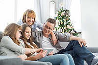 Family using tablet PC on sofa with Christmas tree in background