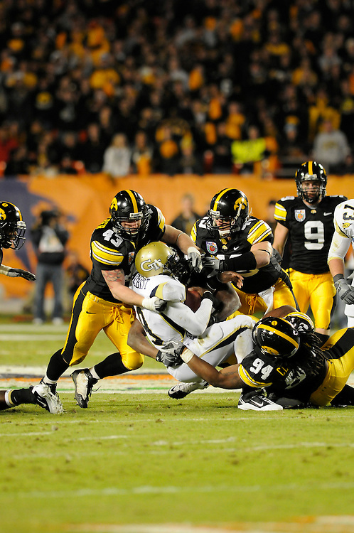 January 5, 2010: Defensive end Adrian Clayborn (94) and linebackers Pat Angerer (43) and A.J. Edds (49) of the Iowa Hawkeyes tackle quarterback Josh Nesbitt of the Georgia Tech Yellow Jackets during the NCAA football game between the Georgia Tech Yellow Jackets and the Iowa Hawkeyes in the Orange Bowl. The Hawkeyes were leading the Yellow Jackets 14-7 at halftime.
