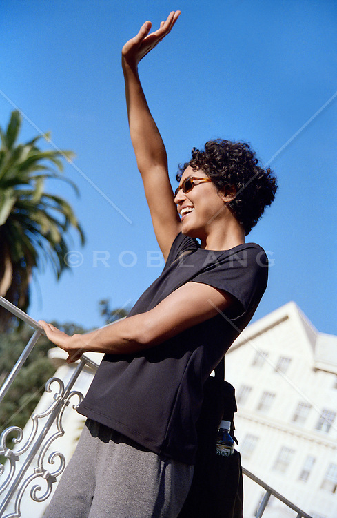 Woman outdoors smiling and waving, San Francisco, CA