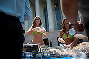 """Wearing a bikini that look like lettuce, PETA's (People for the Ethical Treatment of Animals) """"lettuce ladies,"""" TESSA CALLAN and BRITT MASH, serve vegan hotdogs to passers-by outside the Rayburn House Office Building in Washington, D.C. in celebration of National Veggie Hot Dog Month. PETA aims to draw attention to foods made without animal products"""