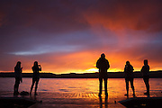 A group of silhouetted people watch a sunset form after a rain storm hits Payette Lake. McCall, Idaho.