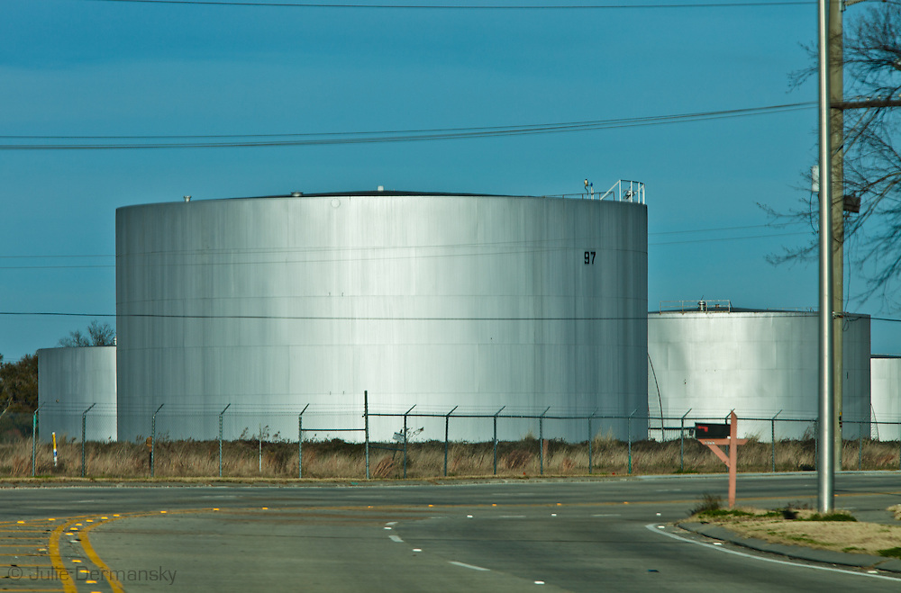 """Exxon Mobile oil tanks in Scotlandville. This site is located in the stretch between Baton Rouge and New Orleans along the Mississippi River has a large concentration of chemical and oil companies and was formerly referred to as the """"petrochemical corridor"""" but now is know as """"cancer alley"""" after numerous cases of cancer occurring in the small rural communities on both sides of the river were reported. The record high levels of the Mississippi River in the spring of 2011 brought on by what some scientists clasify as climate change,  threaten the environment with the potential flooding of industrial complexes and nuclear facilities along the river."""