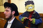 A young Orthodox Jewish boy dressed as Dennis the menace in the congregation during the Megillah reading for Purim in Walford road synagogue. Purim is one of the most entertaining Jewish holidays.  It commemorates the time when the Jewish people living in Persia were saved from extermination from a massacre by Haman. Due to the courage of a young Jewish woman called Esther, it is customary for men dress u and to hold carnival-like celebrations.
