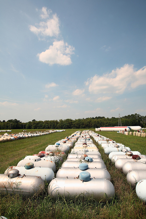 Abandoned propane and liquid Gas tanks in a field.