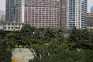 A man works out in a common green area at an apartment complex in Shanghai, China, Saturday, May 30, 2009. Block after city block, towers of concrete, steel and glass fill the skyline. .Teeming and congested, the intensely urban landscapes of China's biggest cities show a glimpse of what the future will hold for the rest of the country.In the sprawling megacities of Beijing, Shanghai and Chongqing, where populations exceed 10 million people, extreme urban density means that the number of people living within a few square blocks here is equal to the population of entire mid-size U.S. cities. .China's urban population soared to 607 million people last year _ nearly equaling the 700 million living in the countryside. The country's headlong plunge toward urbanization continues unabated as tens of millions of migrants from the countryside flood to cities in search of money, jobs and other opportunities