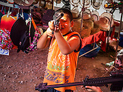 27 JUNE 2014 - DAN SAI, LOEI, THAILAND: Boys play with toy guns during the street fair in Dan Sai during the Phi Ta Khon. Phi Ta Khon (also spelled Pee Ta Khon) is the Ghost Festival. Over three days, the town's residents invite protection from Phra U-pakut, the spirit that lives in the Mun River, which runs through Dan Sai. People in the town and surrounding villages wear costumes made of patchwork and ornate masks and are thought be ghosts who were awoken from the dead when Vessantra Jataka (one of the Buddhas) came out of the forest.    PHOTO BY JACK KURTZ