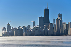© Licensed to London News Pictures. 27/12/2017. CHICAGO, USA.  The John Hancock Center is seen above other tall buildings as the city of Chicago experiences sub-zero temperatures.  With the effects of wind chill, temperatures are expected to be -22C to -32C.  Photo credit: Stephen Chung/LNP