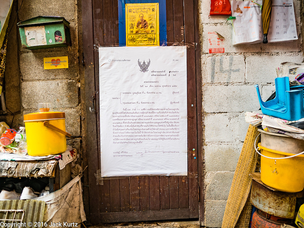 30 JULY 2016 - BANGKOK, THAILAND:  An eviction notice pasted to the door of a resident of the Pom Makahan Fort slum. Residents of the slum have been told they must leave the fort and that their community will be torn down. Mahakan Fort was built in 1783 during the reign of Siamese King Rama I. It was one of 14 fortresses designed to protect Bangkok from foreign invaders. Only of two are remaining, the others have been torn down. A community developed in the fort when people started building houses and moving into it during the reign of King Rama V (1868-1910). The land was expropriated by Bangkok city government in 1992, but the people living in the fort refused to move. In 2004 courts ruled against the residents and said the city could take the land. Eviction notices have been posted in the community and people given until April 30 to leave, but most residents have refused to move. Residents think Bangkok city officials will start evictions around August 15, but there has not been any official word from the city.     PHOTO BY JACK KURTZ