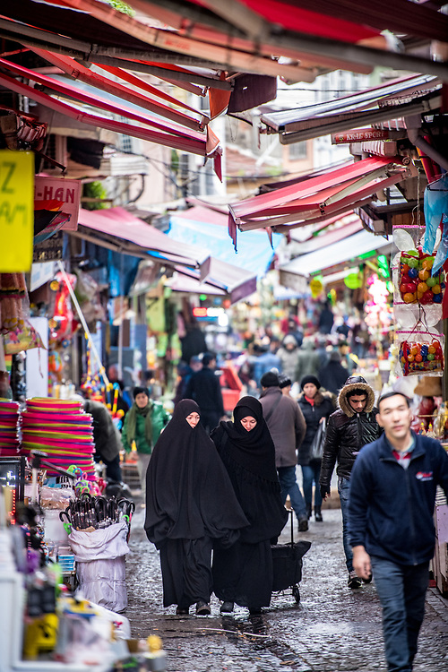 Two women wearing chadors walk along narrow street under awnings in outdoor market , Istanbul, Turkey