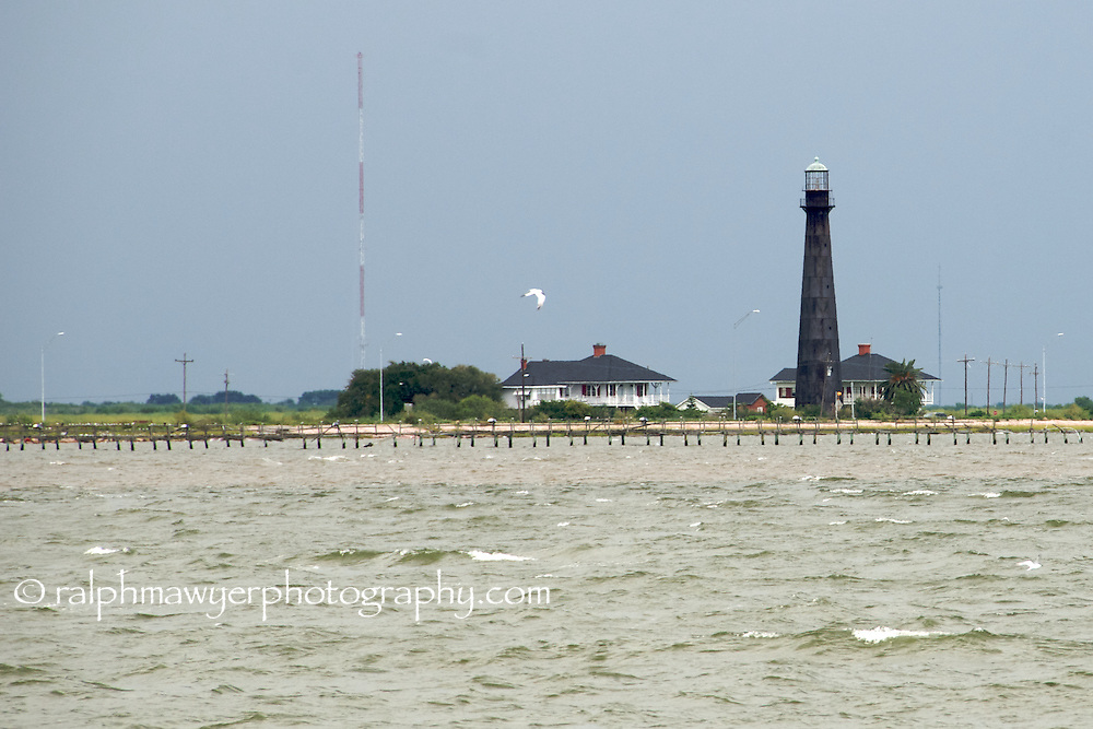 Port Bolivar Lighthouse under  overcast skys. The lighthouse was completed in 1852 and is located at the end of the Bolivar Peninsula, north of Galveston Island at the entrance to Galveston Bay.