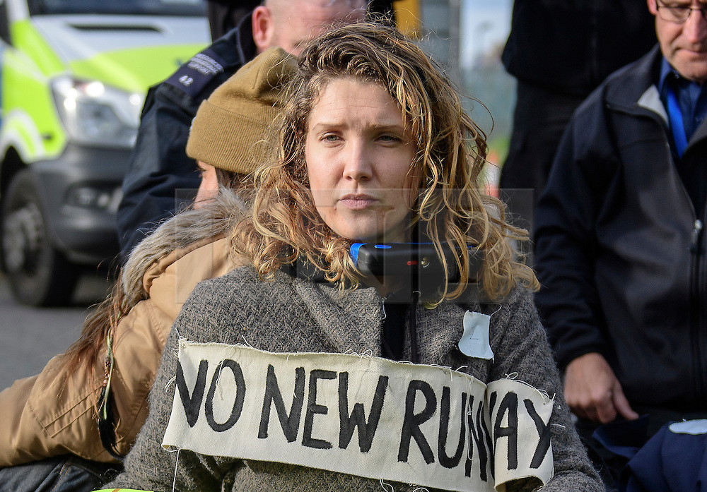 """© Licensed to London News Pictures. 19/11/2016. Heathrow, UK. An activist reported to be SOPHIE LYSACZANKO , wearing the slogan """"NO NEW RUNWAY"""" sits on the road surface, that she and other activists are attached to, near Heathrow Airport. A group of activists stage attach themselves to a road surrounding  Heathrow Airport, during a demonstration against the expansion of Heathrow Airport and the building of a third runway. Some activists  threatened """"direct action"""". Photo credit: Ben Cawthra/LNP"""