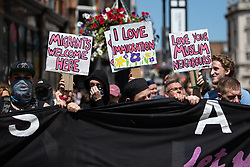 """© Licensed to London News Pictures . 07/07/2018 . Leeds , UK . Anti-fascist counter protesters carrying placards that read """" Migrants welcome here """" , """" I love immigration """" and """" Love your Muslim neighbours """" obstruct Boar Lane in order to block an anti-Islam march by supporters of jailed EDL founder Tommy Robinson , including those from the """" Yorkshire Patriots """" and """" First for Britain """" , in Leeds City Centre . Robinson ( real name Stephen Yaxley-Lennon ) was convicted of Contempt of Court in May 2018 after committing a second offence , whilst serving a suspended sentence for the same crime . Photo credit : Joel Goodman/LNP"""