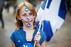 © Licensed to London News Pictures. 18/09/2014. Glasgow, UK. Sarah Dolan, 10, walking in Glasgow city centre with Scottish Saltire flag whilst people of Scotland going to polling stations to vote on the Scottish independence referendum on Thursday, 18 September 2014. Photo credit : Tolga Akmen/LNP