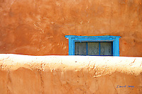 Sun splashed orange adobe wall partially hides turquoise painted wooden window frame, Santa Fe, New Mexico, USA. Window has white lace curtains, and is set in an orange adobe wall.