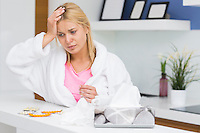 Young woman suffering from cold in kitchen