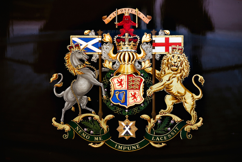 """Escutcheon on the door of the Scottish State Coach, Buckingham Palace Mews, coach museum.  Close up showing the entire motif with flags of England and Scotland, lion, unicorn, crown, quartered royal shield, and the saying """"nemo mi impune lacessit."""""""