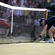 LONDON, ENGLAND - JULY 14: A ball boy retrieves the ball at the net during the Roger Federer of Switzerland against Thomas Berdych of the Czech Republic in the Gentlemen's Singles Semi-final of the Wimbledon Lawn Tennis Championships at the All England Lawn Tennis and Croquet Club at Wimbledon on July 14, 2017 in London, England. (Photo by Tim Clayton/Corbis via Getty Images)