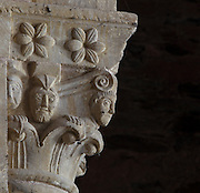 Carved capital depicting foliage designs and human heads, to the right of the organ between the ambulatory and the nave of the Abbatiale Sainte-Foy de Conques or Abbey-church of Saint-Foy, Conques, Aveyron, Midi-Pyrenees, France, a Romanesque abbey church begun 1050 under abbot Odolric to house the remains of St Foy, a 4th century female martyr. The church is on the pilgrimage route to Santiago da Compostela, and is listed as a historic monument and a UNESCO World Heritage Site. Picture by Manuel Cohen