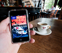 Reading e-book travel guide to Amsterdam with cup of coffee in Amsterdam The Netherlands