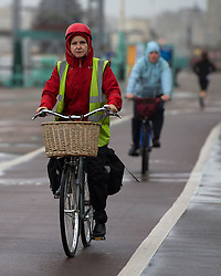 © Licensed to London News Pictures. 15/09/2015. Brighton, UK. Commuters wrapped up on bikes riding to work along Brighton promenade as high winds and heavy rain batter Brighton seafront on  the south coast of England.  Photo credit: Ben Cawthra/LNP