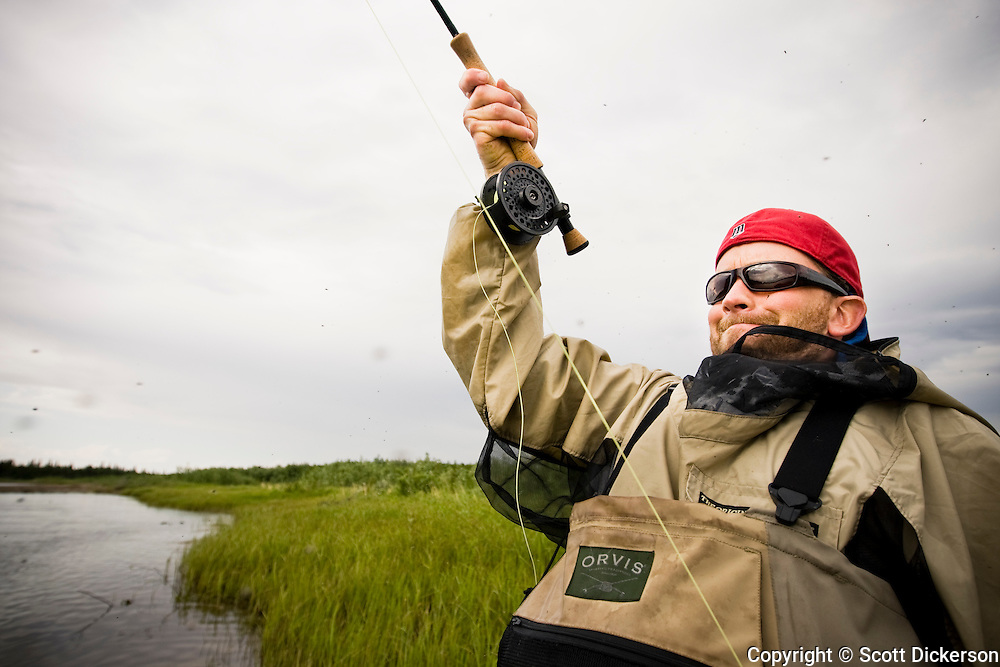 Anders Gustafson with a salmon on the line while fly fishing the Mulchatna River in Bristol Bay, Alaska.