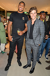 Left to right, ANTHONY JOSHUA and OLIVER CHESHIRE at a party to celebrate the launch of the new Watches of Switzerland Knightsbridge store 47-51 Brompton Road, London on 7th July 2016.
